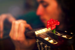 Man playing guitar, guitar with red flowers of carnations. Stock Photography
