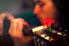 Man playing guitar, guitar with red flowers of carnations. Stock Image