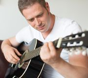 Man playing guitar. Handsome man playing guitar at home Stock Photo