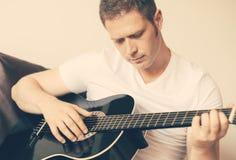 Man playing guitar. Handsome man playing guitar at home Royalty Free Stock Image