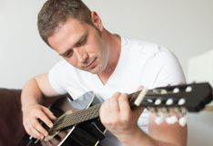 Man playing guitar. Handsome man playing guitar at home Royalty Free Stock Photography