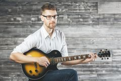 Man playing the guitar. Handsome man playing the guitar on wooden wall background. Music concept Stock Photography