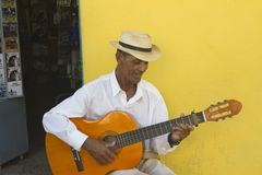 Man Playing the guitar in Trinidad -. A man with a hat segats i front of a door and playing the guitar and singing in a Trinidad street, Cuba Stock Image