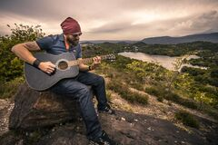 Man playing guitar on hilltop Royalty Free Stock Photos