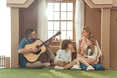 Man playing guitar for his family at new. Cardboard house stock photo