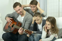 Man playing the guitar for his family Stock Images