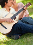 Man playing the guitar while his friend is listening to him Stock Images