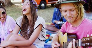Man playing guitar for his friends at a music festival 4k. Happy man playing guitar for his friends at a music festival 4k stock video footage