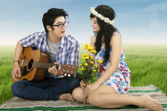 Man playing guitar for his girlfriend. A romantic men playing guitar for his girlfriend shooting outdoors stock photography