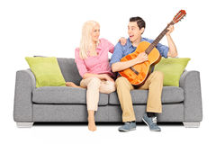 Man playing on guitar with his girlfriend Stock Image