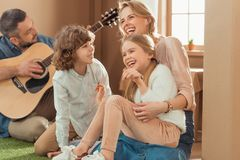 Man playing guitar for his happy family at new. Cardboard house stock image