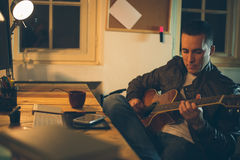 Man playing guitar at home office Royalty Free Stock Images