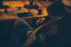 Man playing guitar at home office. Evening/low light shot Stock Photo