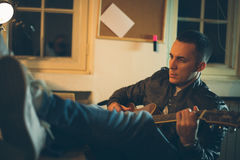 Man playing guitar at home after work Royalty Free Stock Image
