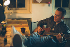 Man playing guitar at home after work Stock Photo