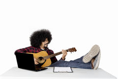 Man playing guitar with laptop on table. Young man playing guitar while listening music with earphone and laptop on table,  on white background Royalty Free Stock Images