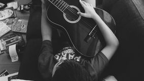 Man Playing Guitar Lying on Couch in Grayscale Photography Stock Photography