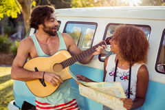 Man playing guitar near campervan and woman holding map beside him Stock Photography