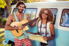 Man playing guitar near campervan and woman holding map beside him Royalty Free Stock Photo