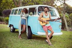 Man playing guitar near campervan and woman photographing beside him Royalty Free Stock Images