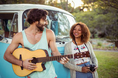 Man playing guitar near campervan while woman standing beside him Royalty Free Stock Photos