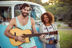 Man playing guitar near campervan while woman standing beside him Stock Image