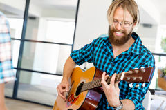 Man playing guitar in office Royalty Free Stock Images
