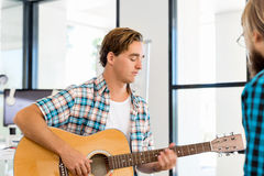 Man playing guitar in office Royalty Free Stock Image