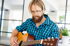Man playing guitar in office Royalty Free Stock Photos