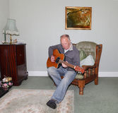 Man playing guitar. Old man playing guitar in his armchair Stock Photography