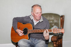 Man playing guitar. Old man playing a traditional acoustic guitar Royalty Free Stock Photos