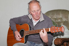 Man playing guitar. Old man playing a traditional acoustic guitar Royalty Free Stock Photo