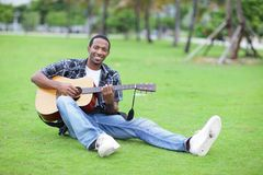 Man playing guitar in the park Royalty Free Stock Image