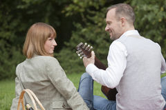 Man playing guitar by picnic Stock Photos