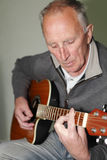 Man playing guitar. Portrait of a senior man playing a traditional acoustic guitar Royalty Free Stock Photo
