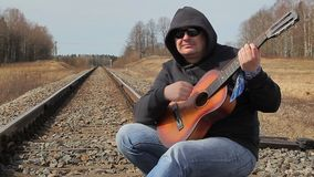 Man playing guitar on the railway stock footage