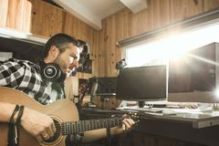 Man playing guitar in a recording studio. Concept guitarist composing music. Man playing guitar in a recording studio. Concept guitarist composing songs stock images