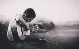 Man playing guitar on roadside Stock Image