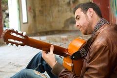 Man playing guitar. Seated young man playing guitar Stock Photos
