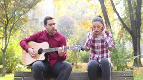 Man playing guitar and singing with women while sitting on bench in park stock video footage