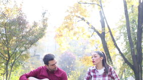 Man playing guitar and singing with women while sitting on bench in park. Handsome man playing guitar and singing with beautiful brunette women while sitting on stock video footage