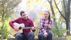 Man playing guitar and singing with women while sitting on bench in park. Handsome man playing guitar and singing with beautiful brunette women while sitting on stock video