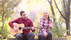 Man playing guitar and singing with women while sitting on bench in park stock video
