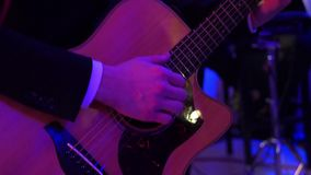 Man playing guitar on a stage musical concert close-up view. Uhd video stock video footage