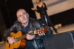 Man playing guitar on stage musical concert. Man playing guitar on a stage musical concert Royalty Free Stock Image