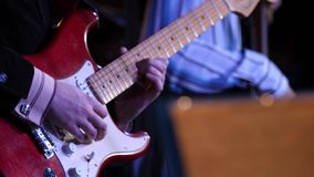 A man is playing guitar on stage. Young man playing on electric guitar close-up. Artist Guitarist hand play electricity stock video footage