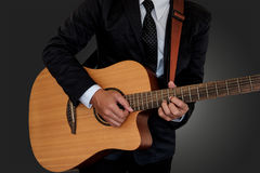 Man playing guitar. Man in suit playing guitar on gray background Stock Photo