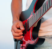 Man playing a guitar at sunset. Close up. Royalty Free Stock Photography