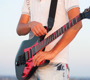 Man playing a guitar at sunset. Close up. Stock Photography