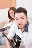 Man playing guitar to girl Stock Photography